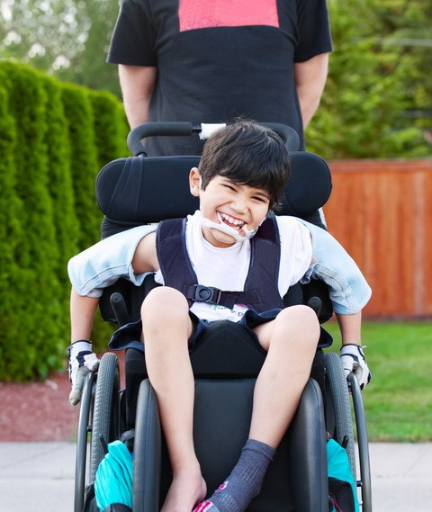Happy little disabled boy wheeling around outdoors in wheelchair